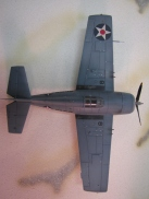 Overhead view shows the wing which is a defining trait of the F4F-3 Wildcat. Unlike later models, it does not have a wing fold (for carrier storage). This feature became important as it was learned that MORE FIGHTERS were always needed on a carrier. It also only has two .50s in each wing. The next model would have three, with less ammunition to save weight. Navy pilots considered this a design flaw. Four .50s were plenty against Japanese aircraft, and less ammunition was bad! The change was requested by the British, who used eight guns in their fighters, and didn't quite understand that the M2 .50 had about four times the kinetic energy of their own MGs. Another big identifying trait is the large panels outboard of the guns. This is for flotation devices (rubberized air bags) that would deploy if the airplane hit the water. This idea was actually abandoned early in Wildcat construction, but the panels remained until the next variant.